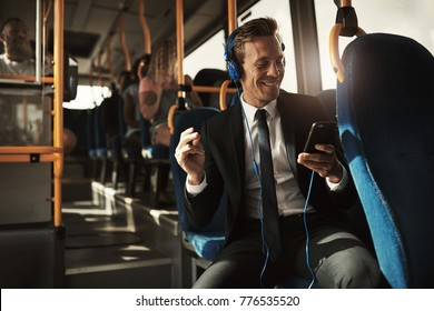 Smiling young businessman sitting on a bus during his morning commute snapping his fingers while listening to music on headphones