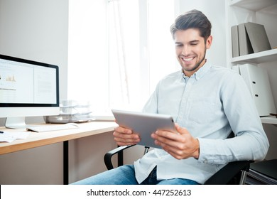 Smiling young businessman sitting at the table and using tablet computer in office