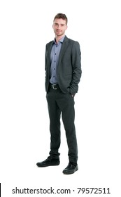 Smiling young businessman standing relaxed with hands in pockets isolated on white background
