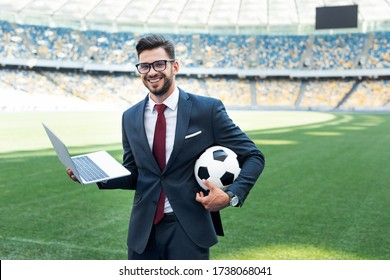 smiling young businessman in suit with laptop and soccer ball sitting on football pitch at stadium, sports betting concept