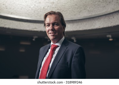 Smiling young businessman with suit and red tie in room.