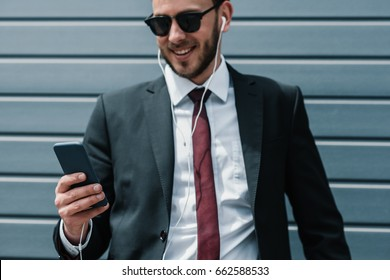 Smiling young businessman in sunglasses and earphones using smartphone