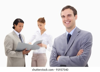Smiling young businessman with talking colleagues behind him against a white background