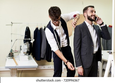 Smiling young businessman talking to his colleague on smartphone while highly professional tailor measuring him in order to make classical suit, interior of modern studio on background