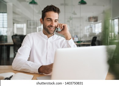 Smiling young businessman talking on his cellphone while working on a laptop at his desk in a modern office