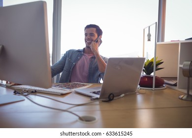 Smiling young businessman talking on mobile phone while working at creative office