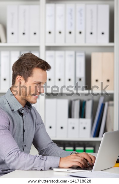 Smiling young businessman using laptop at office desk