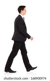 Smiling young businessman walking in black suit. Full length studio shot isolated on white.