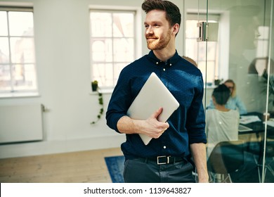 Smiling young businessman walking with his laptop in a modern office with colleagues at work in the background