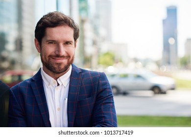 Smiling young businessman wearing a blazer standing confidently in the city with office buildings in the background
