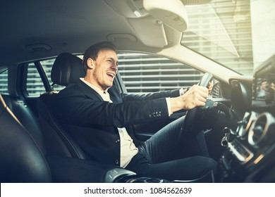Smiling young businessman wearing a blazer singing while driving his car through the city during his morning commute to work