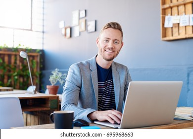 Smiling young businessman wearing a blazer sitting alone at his desk in a large modern office working online with a laptop