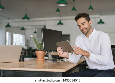 Smiling young businessman working online with a digital tablet while sitting at his desk in a large modern office