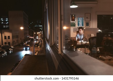 Smiling young businessman working overtime at a desk late at night behind office building windows reflecting the city