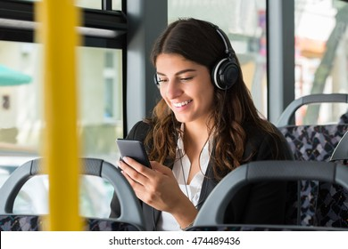 Smiling Young Businesswoman With Cellphone Listening Music While Traveling By Bus