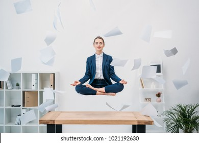 smiling young businesswoman with closed eyes meditating while levitating at workplace with papers