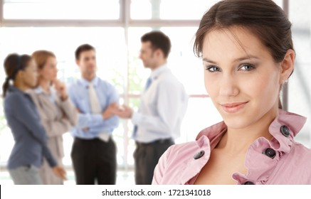 Smiling young businesswoman in front business team in background.