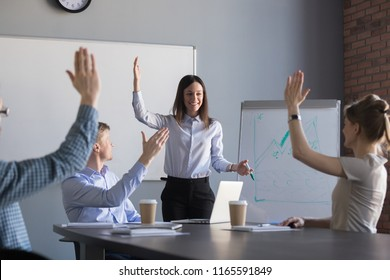 Smiling young businesswoman giving corporate training for diverse work group, employees raising hands taking part in team building activity or answering question during flipchart presentation