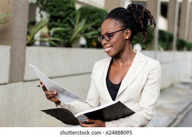 Smiling young businesswoman holding records must meet her partner for a contract