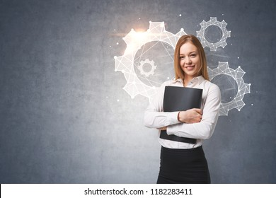 Smiling young businesswoman hugging a folder standing near a concrete wall with cogwheels and gears on it. Teamwork concept. Toned image mock up