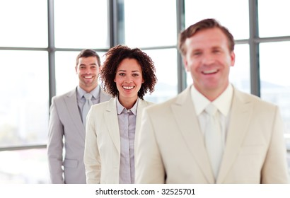 Smiling young businesswoman in a line with her colleagues