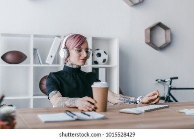 smiling young businesswoman listening music in headphones and holding paper cup at workplace
