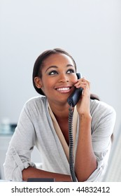 Smiling young businesswoman on phone looking upward. Business concept.