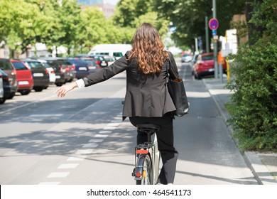 Smiling Young Businesswoman Pruning On Bicycle Riding On Street