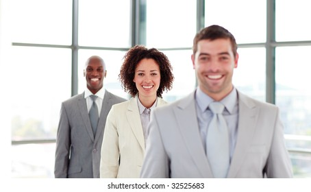 Smiling young businesswoman in a row with her colleagues