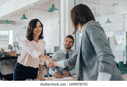 Smiling young businesswoman shaking hands with a coworker during a meeting with colleagues around a table in an office boardroom