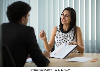 Smiling young businesswoman showing contract to partner. Young Caucasian manager having meeting with client, explaining agreement to him. Partnership and meeting concept