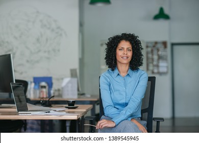 Smiling young businesswoman sitting alone at her desk while working on a laptop in a large modern office