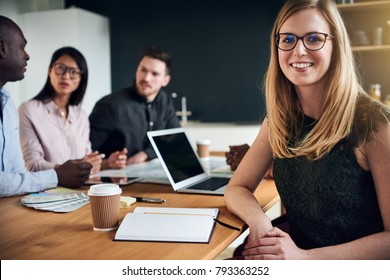 Smiling young businesswoman sitting at a boardroom table during a meeting with colleagues in the background