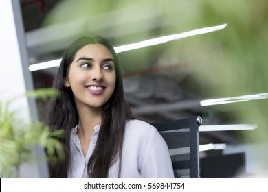 Smiling young businesswoman sitting at computer