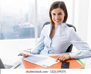 Smiling young businesswoman sitting at office desk and reviewing financial reports, accounting and business management concept