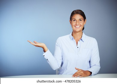Smiling Young Businesswoman Sitting On Her Table Showing Something