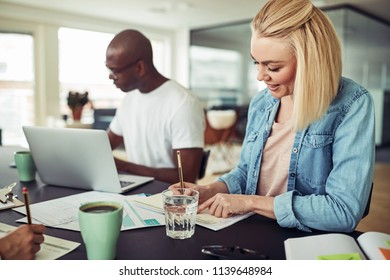 Smiling young businesswoman sitting at a table writing down notes while working with colleagues in a modern office