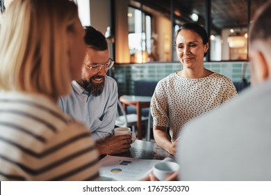 Smiling young businesswoman talking with a group of colleagues over coffee during their office break
