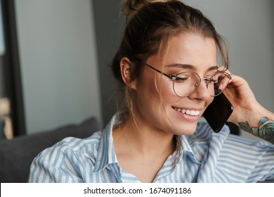 Smiling young businesswoman talking on mobile phone while relaxing on a couch at home
