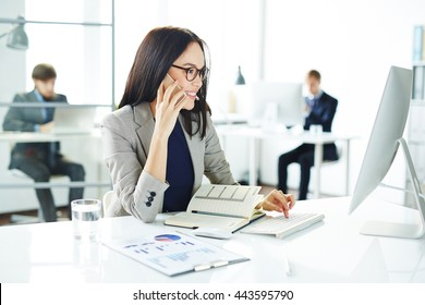 Smiling young businesswoman talking on the phone and typing on computer at the table