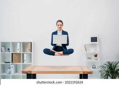 smiling young businesswoman using laptop while levitating in office