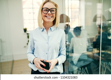 Smiling young businesswoman wearing glasses standing with a cellphone in a modern office with colleagues at work in the background