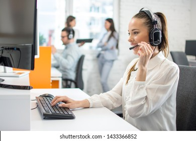 Smiling young businesswoman working with colleagues in a call center office, technical support operators.