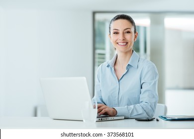 Smiling young businesswoman working at office desk and typing on a laptop, she is looking at camera