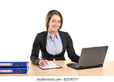 A smiling young businesswoman working on a laptop isolated on white background