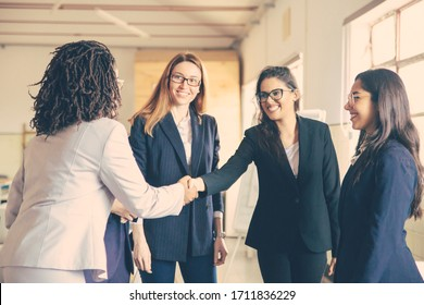 Smiling young businesswomen shaking hands in office. Confident cheerful business partners greeting each other. Business concept