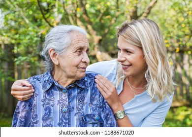 Smiling young caretaker walking with senior lady in the garden
