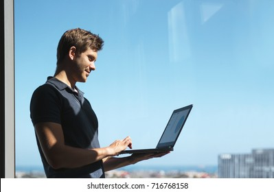 Smiling young casual businessman holding and using laptop with blurred city background
