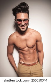 Smiling young casual man posing shirtless with both hands in his pocket.