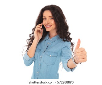 smiling young casual woman talking on the phone and making the ok thumbs up hand sign